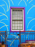 房子的蓝色墙壁有紫色窗口的 与小门的门廊 免版税库存图片