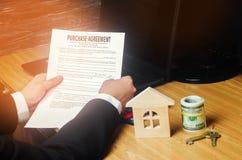 房子的购买的合同 钥匙、房子模型和美元 物产投资 买,租赁和卖公寓 库存照片