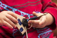 房子的钥匙对于儿童` s手 免版税库存图片