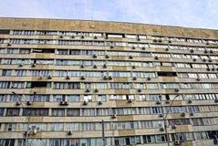 房子的门面有公寓和窗口的是灰色棕色的在天空的背景中 免版税库存照片