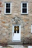 房子的门面有白色前门和两个窗口的 免版税图库摄影