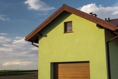 房子的鲜绿色的门面有一个可看见的屋顶下端背面、窗口和车库门的 在背景中与clou的好的蓝天 库存图片