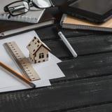 房子的建筑的计划 有企业对象的办公桌-开放笔记本,片剂计算机,玻璃,统治者,写作a 库存图片