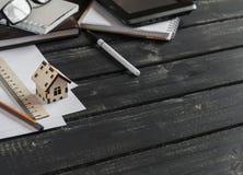 房子的建筑的计划 有企业对象的办公桌-开放笔记本,片剂计算机,玻璃,统治者,笔 免版税库存照片