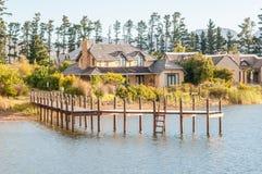 房子看法在一个水坝旁边的有跳船的 免版税库存照片