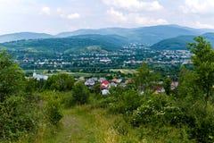房子行在绿色山谷的一个镇在小山和山之间在天际 免版税图库摄影