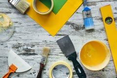 房子装饰的油漆与刷子和辅助部件在书桌上 库存图片