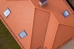 房子金属木瓦屋顶、砖烟囱和小塑料顶楼窗口空中顶视图  屋顶、修理和改造工程 免版税库存照片