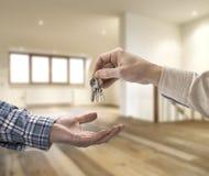 给房子钥匙的地产商买家在顶楼屋子里 免版税库存照片