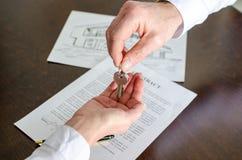 给房子钥匙的房地产经纪商顾客 免版税库存照片