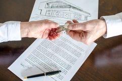 给房子钥匙的房地产经纪商顾客 免版税库存图片