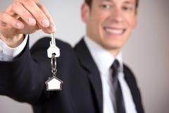 给房子钥匙的年轻商人 免版税图库摄影
