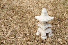 房子Sculptuer有一个中国式屋顶的在干燥草皮 免版税库存照片
