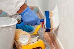房屋油漆工在绘有刷子的工作墙壁 免版税库存照片