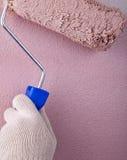 房屋涂料画家使用墙壁的漆滚筒 免版税库存图片