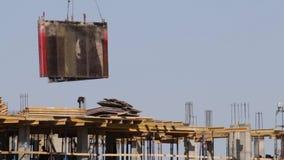房屋结构的建筑由混凝土制成 在建筑工人移动 塔吊举装载 股票录像