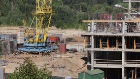 房屋结构的建筑由混凝土制成 在建筑工人移动 工作一架塔吊,卡车移动 股票录像