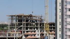 房屋结构的建筑由混凝土制成 在建筑工人移动 工作一架塔吊 股票录像