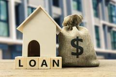 房屋贷款,抵押,家庭保险,房子概念的财政抵押 在袋子的美元金钱和在木的住宅模型 免版税库存图片