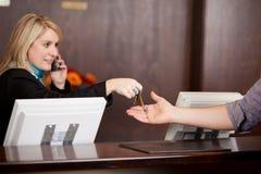 给房间钥匙的年轻接待员顾客 库存照片