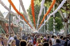 所有年龄的人人群获得乐趣和公平地散步在塞维利亚` s 4月的 免版税库存照片