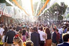 所有年龄的人人群获得乐趣在日落和穿戴在传统服装在塞维利亚` s 4月市场 免版税库存图片