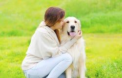所有者和愉快的金毛猎犬在草一起尾随 免版税库存照片