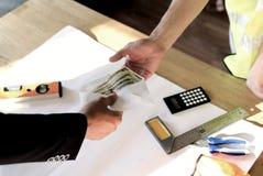 所有者或上司手顶视图捐钱的给雇员或雇用的人他的薪水或薪金的在桌 付款在纸 库存图片