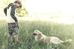 年轻所有者教他的狗棍子比赛  库存图片
