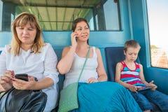 所有年龄的三位乘客在火车地铁的 库存图片