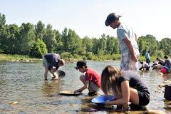 所有年龄的金探油矿者在Gardon河的河岸的 免版税库存照片