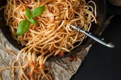扁面条用红色调味汁和在生铁平底锅的新鲜的蓬蒿 库存图片