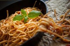 扁面条用红色调味汁和在生铁平底锅的新鲜的蓬蒿 免版税库存图片