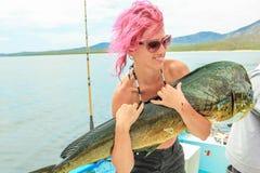扁鲨粉发的女孩拿着一条鱼Dorado 免版税库存照片