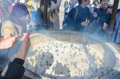 扇动在他们自己的香火烟的香罐的未认出的人为身体好在Senso籍寺庙 免版税图库摄影