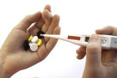手、温度计和药片 免版税库存图片