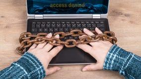 手、膝上型计算机键盘和老生锈的链子特写镜头在木背景 免版税库存图片