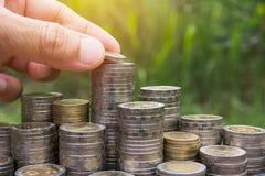手下落与金钱生长为事务的硬币堆的一枚硬币 飞翅 免版税库存照片