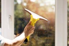 手与吸尘器的清洁窗口 免版税库存图片
