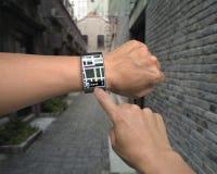 手与地图指南的穿戴smartwatch 库存照片