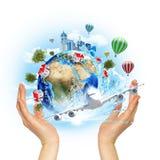 手与大厦和树的举行地球 免版税库存照片
