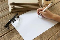 手与纸的候宰栏在木桌上 免版税库存图片
