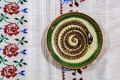 手与装饰陶瓷板材的被绣的桌布 得体 免版税图库摄影