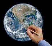 手与铅笔的图画地球 免版税库存图片