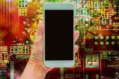 手两次曝光拿着流动智能手机的和电子线路上 库存照片