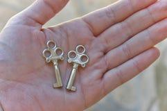 手中两把微小的钥匙 库存图片
