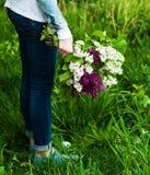 手中开花的淡紫色的花 免版税库存图片
