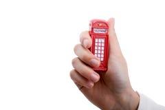 手中的电话亭 免版税库存照片