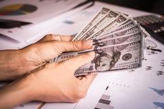 手中金钱银行美国美元有日落背景 库存图片