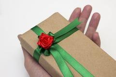 手为假日拿着一件礼物,包装在纸,并且栓与与一朵红色花的一条绿色丝带上升了 库存图片